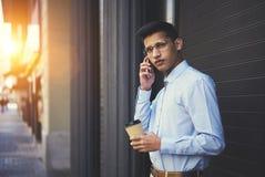 Ritratto di bello studente intelligente nell'abbigliamento casual che chiama al suo amico via cellulare Fotografie Stock