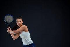 Ritratto di bello tennis della ragazza con una racchetta su fondo scuro Immagine Stock