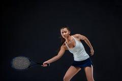 Ritratto di bello tennis della ragazza con una racchetta su fondo scuro Fotografie Stock Libere da Diritti