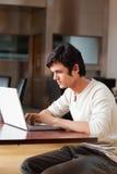 Ritratto di bello uomo che per mezzo di un computer portatile Immagine Stock