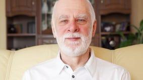 Ritratto di bello uomo senior sorridente bello in maglietta bianca di polo che si siede sul sofà a casa stock footage