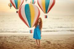 Ritratto di concetto della ragazza del piccolo bambino con capelli rossi e le lentiggini che stanno su una spiaggia con la mongol Fotografia Stock