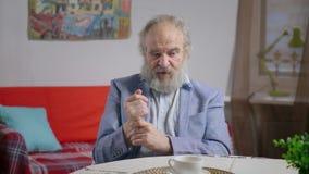 Ritratto di disagio ritenente pensionato barbuto dell'uomo in caffè stock footage