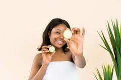 Ritratto di divertimento di bello modello dell'africano nero con pelle liscia che tiene una fetta del cetriolo al suo occhio, rin fotografie stock