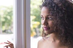 Ritratto di donna abbastanza giovane del mulatto che esamina finestra Fotografie Stock