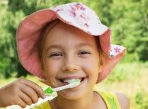 Ritratto di estate dei denti di spazzolatura della bambina adorabile Fotografia Stock