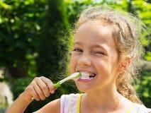 Ritratto di estate dei denti di spazzolatura della ragazza sveglia Fotografia Stock