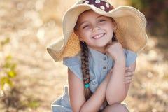 Ritratto di estate di una bambina in un grande cappello Fotografie Stock Libere da Diritti