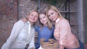 Ritratto di famiglia amorevole, madre felice si diverte a parlare con le figlie e abbracciarsi mentre si rilassava a casa stock footage