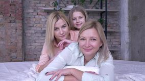 Ritratto di famiglia felice, femmina sorridente con bellissime figlie adulte e bambine sdraiate a letto mentre si rilassano a cas archivi video