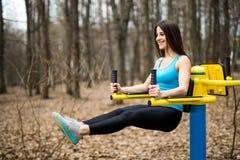 Ritratto di forte giovane donna che appende sulle barre di parete con i suoi vantaggi La donna di forma fisica che esegue la gamb Fotografia Stock