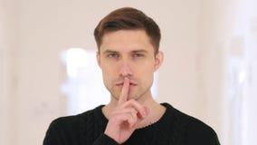 Ritratto di Gesturing del silenzio dall'uomo che si siede nell'ufficio Fotografie Stock Libere da Diritti