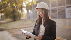 Ritratto di giovane architetto femminile caucasico che sta sul cantiere, tenendo lavagna per appunti e scrittura video d archivio