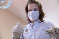 Ritratto di giovane assistente femminile del dentista con gli strumenti medici dentro Immagine Stock