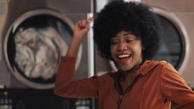 Ritratto di giovane ballare divertente sorridente della donna afroamericana nella lavanderia del pubblico di self service video d archivio