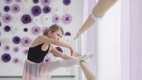 Ritratto di giovane ballerina che allunga fuori vicino alla sbarra di balletto nello studio video d archivio
