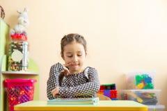 Ritratto di giovane bambina adorabile che legge un libro nell'asilo Bambina espressiva che pensa allo smth immagini stock libere da diritti