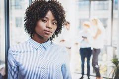 Ritratto di giovane bella azienda leader femminile africana con il gruppo che sta sul fondo in ufficio moderno orizzontale Fotografia Stock