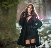 Ritratto di giovane bella donna all'aperto nel paesaggio di inverno Castana sensuale con le gambe lunghe nella posa nera delle ca Immagine Stock