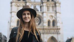 Ritratto di giovane bella donna in cappello che sta vicino alla cattedrale di Notre Dame Parigi, in Francia e lo sguardo alla mac stock footage