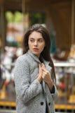 Ritratto di giovane bella donna castana malinconica in un cappotto grigio su un fondo confuso del carosello Fotografie Stock