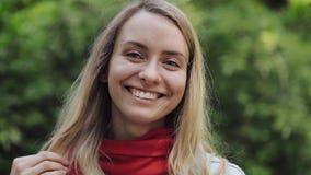 Ritratto di giovane bella donna che indossa in rosso condizione della sciarpa nel parco della città e che esamina la macchina fot video d archivio