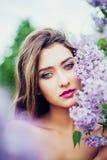 Ritratto di giovane bella donna che posa fra gli alberi lilla Immagini Stock Libere da Diritti