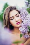 Ritratto di giovane bella donna che posa fra il lillà Occhi chiusi Immagine Stock