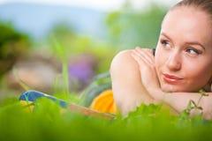 Ritratto di giovane bella donna che si trova nell'erba Fotografia Stock