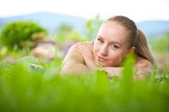 Ritratto di giovane bella donna che si trova nell'erba Immagini Stock