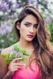 Ritratto di giovane bella donna che tiene un ramo lilla Immagine Stock