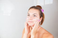 Ritratto di giovane bella donna che usando la crema dei cosmetici Fotografie Stock