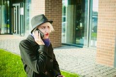 Ritratto di giovane bella donna con capelli bianchi, in un cappotto nero, in una gonna ed in un black hat, parlando sul telefono  Fotografie Stock