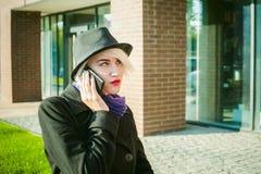 Ritratto di giovane bella donna con capelli bianchi, in un cappotto nero, in una gonna ed in un black hat, parlando sul telefono  Fotografia Stock Libera da Diritti
