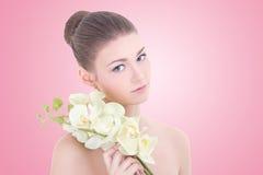 Ritratto di giovane bella donna con il fiore dell'orchidea sopra il rosa Fotografia Stock