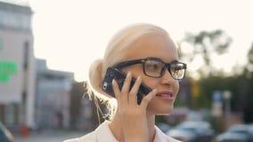 Ritratto di giovane bella donna di affari che fa una telefonata all'aperto archivi video