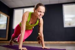 Ritratto di giovane bella donna di forma fisica che fa posizione della plancia all'interno alla palestra sulla stuoia viola di yo Fotografia Stock