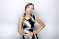 Ritratto di giovane bella donna impertinente nella macchina fotografica esaminante sprezzante della camicia a strisce che posa pe Immagini Stock