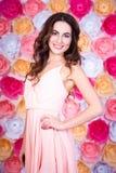Ritratto di giovane bella donna sopra il fondo dei fiori Immagini Stock