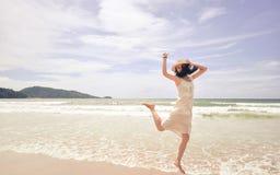 Ritratto di giovane bella donna sorridente che salta sulla spiaggia fotografia stock