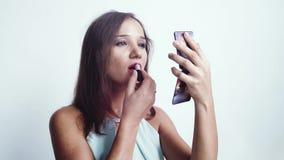 Ritratto di giovane bella lucentezza del labbro della pittura della donna dalle labbra e di sguardo in specchio piccolo a disposi stock footage