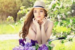 Ritratto di giovane bella ragazza in cappello con capelli lunghi con la merce nel carrello dei fiori sulla bici d'annata Donna mo Immagine Stock Libera da Diritti