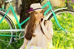 Ritratto di giovane bella ragazza in cappello con capelli lunghi con la merce nel carrello dei fiori sulla bici d'annata Donna mo Immagini Stock Libere da Diritti