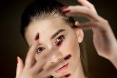 Ritratto di giovane bella ragazza castana con trucco naturale che tiene le sue dita davanti al suo fronte fotografia stock