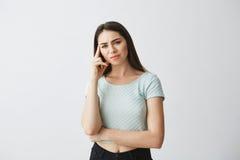 Ritratto di giovane bella ragazza che esamina pensiero aggrottante le sopracciglia della macchina fotografica con il dito sul tem Immagine Stock