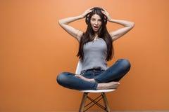 Ritratto di giovane bella ragazza che si siede nella sedia e che ascolta la musica tramite la cuffia avricolare, le sue mani su l fotografie stock libere da diritti
