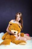 Ritratto di giovane bella ragazza con capelli lunghi in un vestito bianco con i fiori in pantofole rosse nello studio su un backg Fotografie Stock