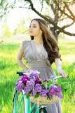 Ritratto di giovane bella ragazza con capelli lunghi in vestito luminoso con la merce nel carrello dei fiori sulla bici d'annata  fotografia stock libera da diritti
