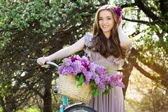 Ritratto di giovane bella ragazza con capelli lunghi in vestito luminoso con la merce nel carrello dei fiori sulla bici d'annata  Fotografia Stock