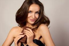 Ritratto di giovane bella ragazza con capelli ricci scuri, spalle nude che tengono una barra di cioccolato per godere del gusto e fotografia stock libera da diritti